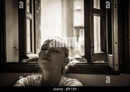 pensive young woman with closed eyes lost in thoughts relaxing and dreaming near opened  window in black and white - Stock Photo