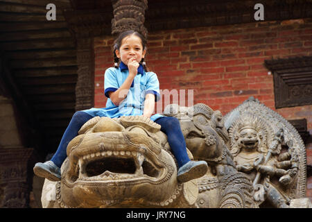 Young Nepalese girl sitting on the statue of a lion in Bhaktapur. - Stock Photo