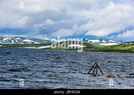 Snow covered mountains behind freshwater lake on a windy day. Rainclouds over the landscape. Location Hardangervidda - Stock Photo
