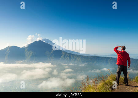 Man on the top of the hill watching wonderful scenery in mountains during summer colorful sunrise in one of the - Stock Photo