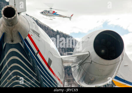 A helcopter is flying over a private jet and snowy mountains - Stock Photo