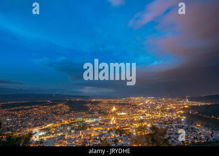 Tbilisi, Georgia. Picturesque Panoramic Aerial Cityscape In Bright Yellow Evening Illumination Under Dramatic Blue - Stock Photo