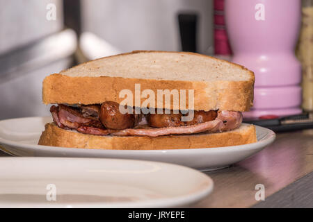 Sausage and bacon sandwich on white bread - Stock Photo