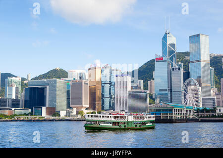 A ferry cruises Victoria harbour at Tsim Sha Tsui in Hong Kong, with the modern skyscrapers of the Central District - Stock Photo