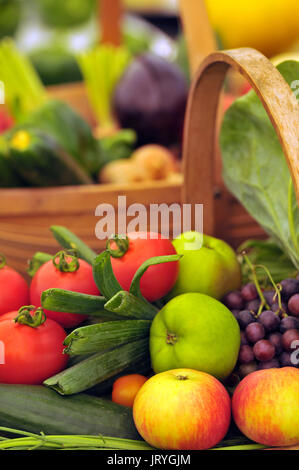 a large basket or trug of mixed fresh organic vegetables on display for sale and appetising healthy diets and detox - Stock Photo