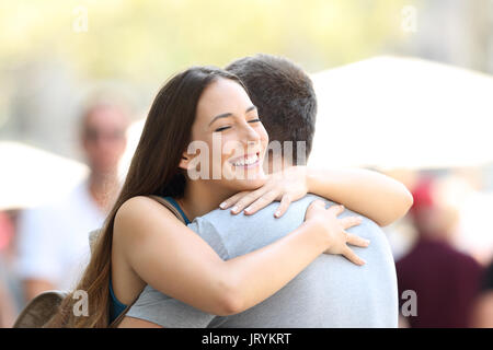 Happy couple or friends hugging on the street after encounter - Stock Photo