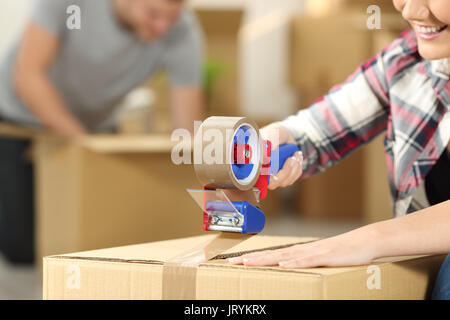 Close up of a happy couple moving home packing boxes and sealing with tape sitting on the floor - Stock Photo