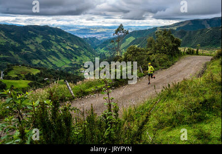 A young male trail runner in a green valley near Cuenca, Ecuador. - Stock Photo