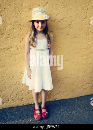 Girl , child kid wearing a straw hat with a sunflower and white summer dress standing at a yellow wall in Nice, - Stock Photo