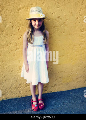Blonde Girl , child kid wearing a straw hat with a sunflower and white summer dress standing at a yellow wall in - Stock Photo