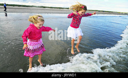 Two girls,children great fun jumping over waves laugh out loud Ireland happy living happy life childhood best times - Stock Photo