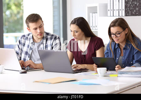 Three attentive employees working on line together with multiple devices at office - Stock Photo