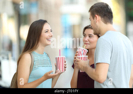 Three happy friends talking and drinking takeaway refreshments standing in the street - Stock Photo