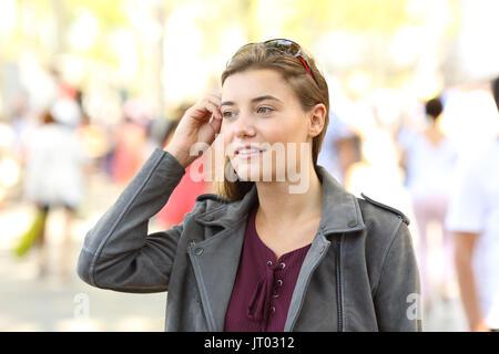 Portrait of a pretty teen looking away walking on the street - Stock Photo