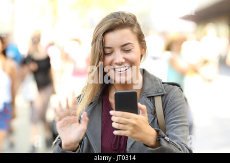 Front view portrait of a happy teen greeting during a videocall on the street - Stock Photo