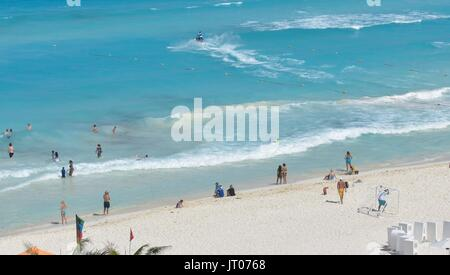 People enjoying activities on the beach on a sunny day in Cancun - Stock Photo