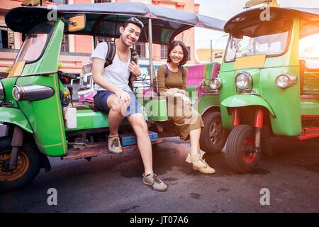 couples of young traveling people sitting on tuk tuk bangkok thailand - Stock Photo