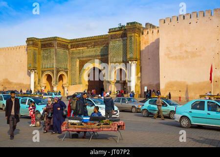 Street life scene. La Bab Mansour or Bab Masour el-Aleuj door, Lahdim Square. Old Imperial City Gate built in 1732 - Stock Photo