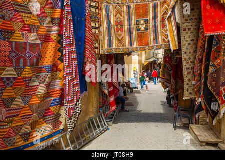 Street life scene. Carpets with traditional patterns for sale at a souq market, bazaar. Souk Medina of Fez, Fes - Stock Photo