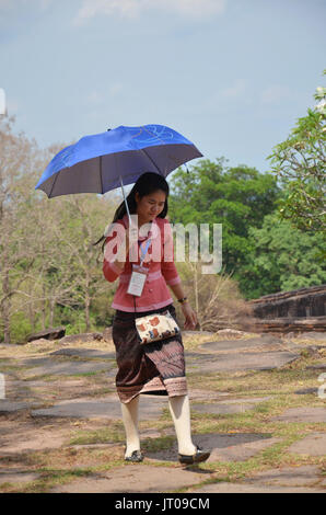 Laos woman guided tour walking and hold umbrella at archaeological site at Vat Phou or Wat Phu of UNESCO World Heritage - Stock Photo