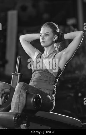 Woman doing strength exercises for abdominal muscles at indoor sport gym. Girl doing yoga stretches after running. - Stock Photo