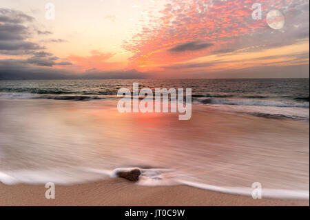 Ocean sunset is a nature beach scenic with a cloud filled sunset sky rush of ocean water breaking on the shore and - Stock Photo
