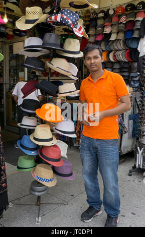 Portrait of a young man from Bangladesh who sells souvenirs and hats to tourists on St. Marks Place in the East - Stock Photo