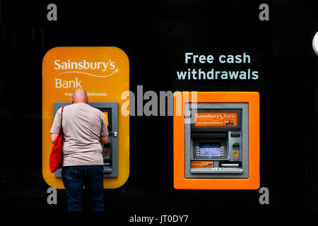 A Man Withdraws Cash From An ATM, Brighton, Sussex, UK - Stock Photo