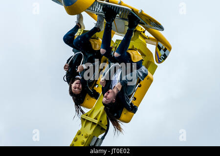 Two Young Women Enjoying A Fairground Ride In The Rain On Brighton Pier, Brighton, East Sussex, UK - Stock Photo