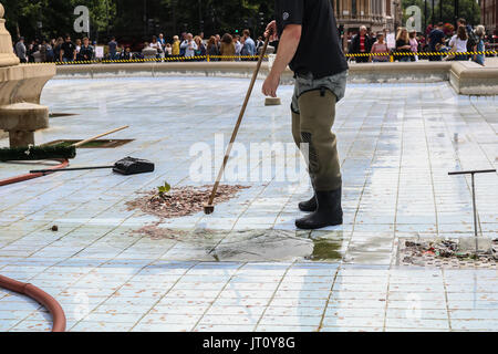 London UK. 7th August 2017. A council worker sweeps and gathers the coins thrown by members of the public whilst - Stock Photo