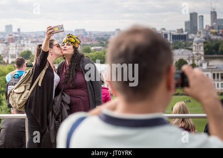 London, UK. 7th Aug, 2017.UK Weather: Tourists take photos and phone selfies from top of Greenwich Park in the overcast - Stock Photo
