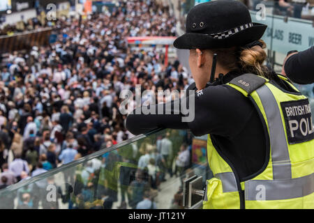 London, UK. 07th Aug, 2017. Transport police watch from the Mezzanine as crowds reach a peak on the concourse after - Stock Photo