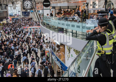 London, UK. 07th Aug, 2017. Transport police with tasers watch from the Mezzanine as crowds reach a peak on the - Stock Photo