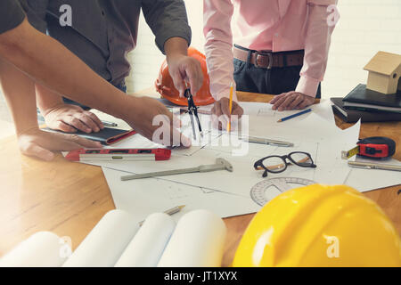 Engineer and Architect concept, Engineer Architects office team working and discussing house plan with blueprints - Stock Photo