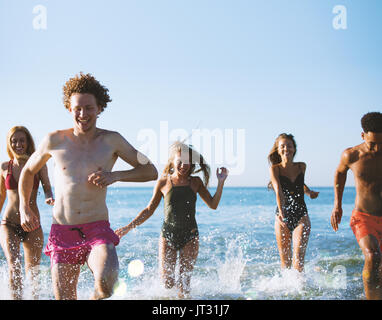 Group of friends run in the sea. Concept of summertime - Stock Photo
