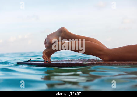 Happy girl in bikini have fun before surfing Surfer lie on surf board. Close up bare legs. Woman in water sport - Stock Photo
