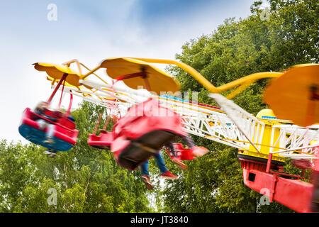 people having fun in amusement park carousel. motion blur - Stock Photo