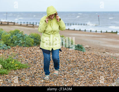 Elderly / Middle aged woman on a beach on a cold windy day in the UK. - Stock Photo