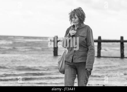 Elderly / Middle aged woman walking by the sea on the coast on a windy day in the UK. Black & White image. - Stock Photo