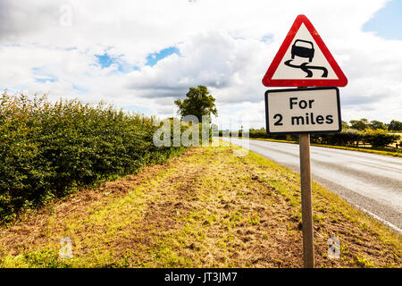 Slippery road, Slippery road UK road sign, for 2 miles, Slippery road for 2 miles, road sign, warning, danger, beware, - Stock Photo