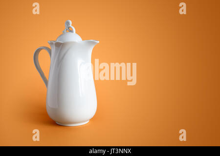 White ceramic milk jug on nice brown background with free space for text - Stock Photo