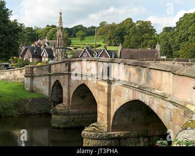 Stone arch bridge over River Manifold with village of Ilam beyond, Derbyshire, England, UK - Stock Photo
