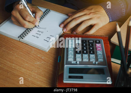 hand Asian man calculate finances and accounting for monthly expenses / charges or cost on notebook with accessories - Stock Photo