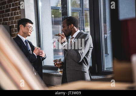 Confident businessman drinking alcohol beverage and smoking cigar while colleague hiding money into suit pocket, - Stock Photo