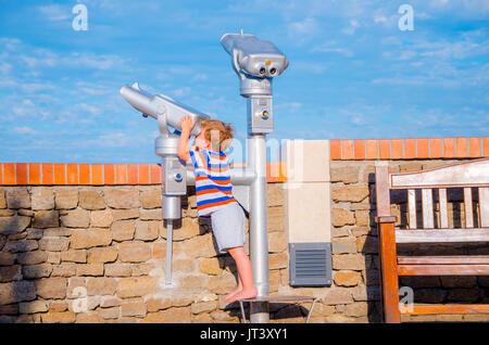 Child looks through telescope on sunny day in summer, vacation scene - Stock Photo