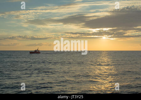 small boat on sunset light going to port in Riga,Latvia, industrial transportation background - Stock Photo