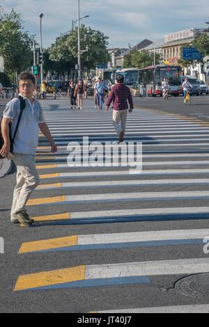 Pedestrians across 3D zebra crossing in central Beijing, China. 07-Aug-2017 - Stock Photo