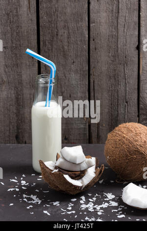 coconut pieces with flakes and milk in glass bottle with straw, coconut drink - Stock Photo