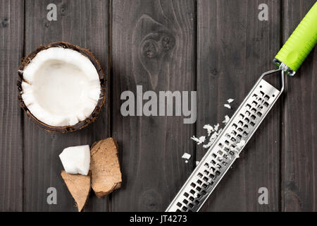 top view of coconut pieces with grater on wooden background, coconut shavings - Stock Photo