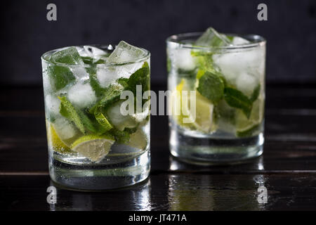 Close-up view of mojito cocktail in glasses on dark wooden table, cocktail drinks concept - Stock Photo